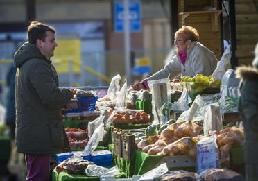 A market trader serving a customer.