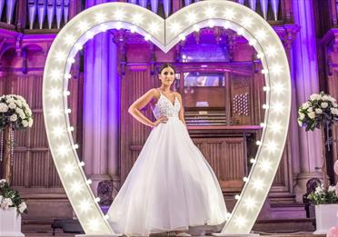 A bride posing in a giant illuminated heart.