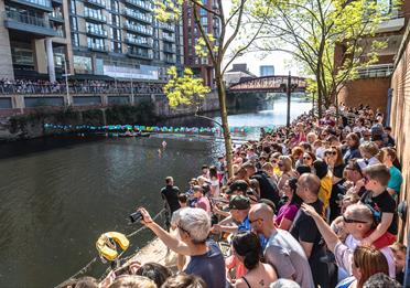 Manchester Duck Race with crowds on the banks of the Irwell.