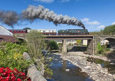 East Lancashire Railway train travelling over countryside bridge