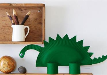 A dinosaur model made from a paper plate and crafting materials.